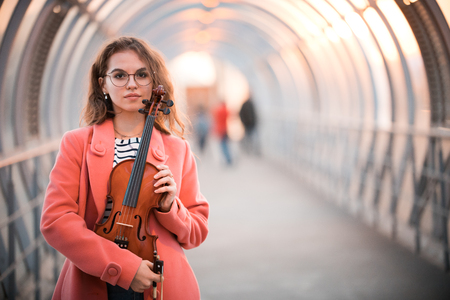 Young woman in glasses standing on the upper pedestrian crossing in a sunset holding a violin