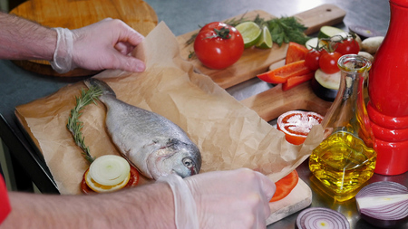 A chef in the kitchen cutted tomato and lemon for fish filling