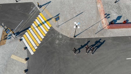 Aerial view of urban streets. Three men walking on the road Stock Photo