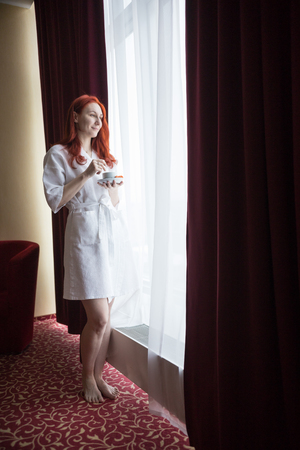 A ginger smiling woman standing by the window and holding a cup of coffee