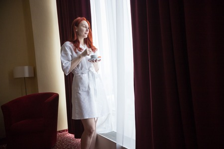 A ginger woman standing by the window in the hotel room and holding a cup of coffee