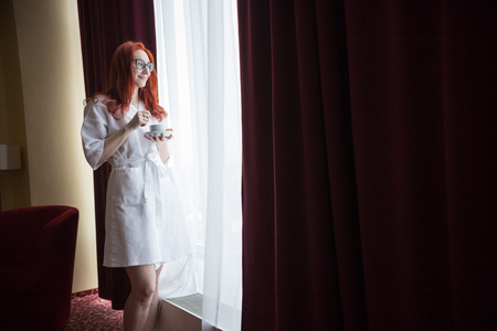A redhead woman standing by the window in the hotel room and holding a cup of coffee