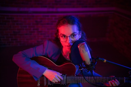 A young woman in glasses playing guitar and singing by the mic in neon lighting