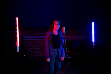 Backstage. A young woman in glasses standing by the microphone in neon lighting