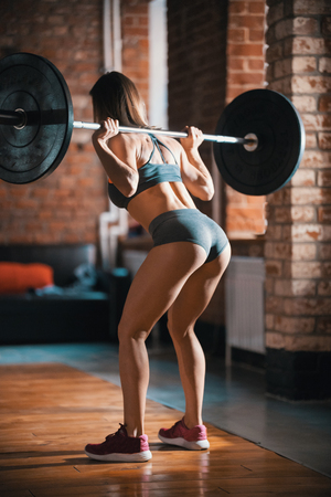 A fit woman training in the gym. Performing squats with a dumbbell on her back