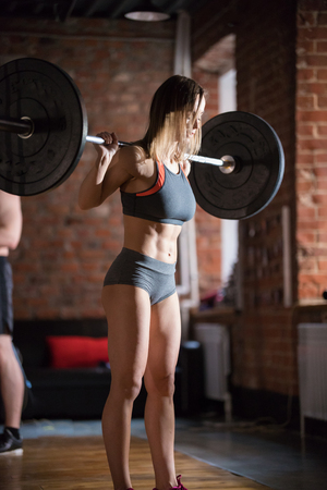 An athlete woman training in the gym. Pumping her butt with a dumbbell on the back