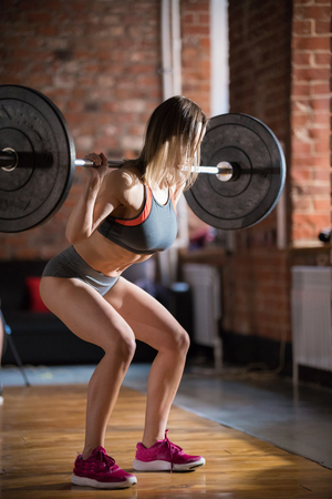 A woman training in the gym. Pumping her butt with a dumbbell on the back