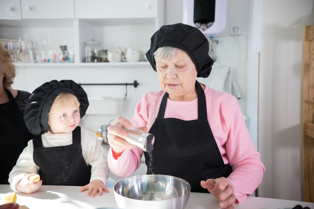 Family making pancakes. An old woman salting the dough Stock Photo