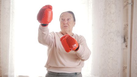 An old emotional woman in boxing gloves is ready to fight