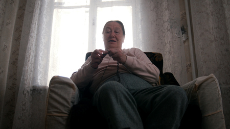 A portrait of an old woman in armchair knitting
