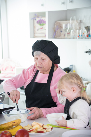 A little girl and her grandmother serving pancakes with sour cream