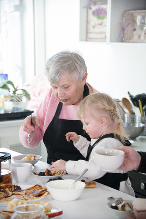 Happy family. A little girl and her grandmother cooking in the kitchen
