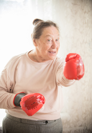 An old smiling woman in sweater and boxing gloves