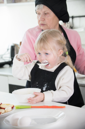 A little girl sloppy eating a sour cream while her grandmother making pancakes