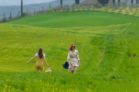 Two women walking on a bright green meadow. One woman holding a hat