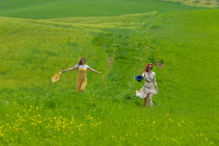 Two women walking on a bright green meadow