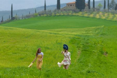 Two happy women walking on a bright green meadow Stockfoto