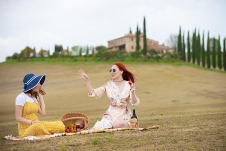 Zwei Frauen sitzen auf der Decke und machen ein Picknick, reden und essen Obst