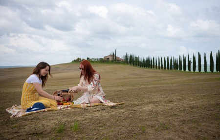 Two women sitting on the blanket having a picnic on the background of the cypress trees. Pouring a wine in the glasses
