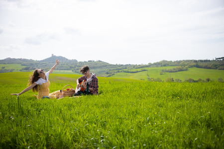 A young couple in bright clothes sitting on a bright green meadow and the man playing guitar while his happy girlfriend having fun