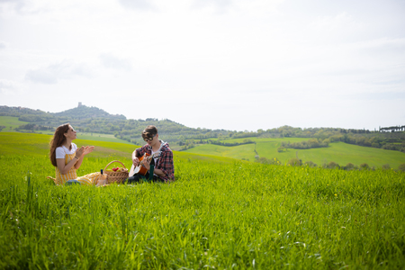A young couple in bright clothes sitting on a bright green meadow and drinking wine. A man playing guitar