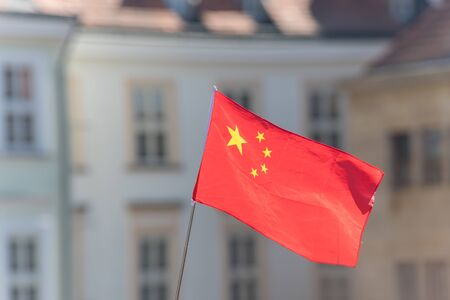 PRAGUE, CZECH REPUBLIC 16-04-2019: China flag waving in the wind against blurred historic building