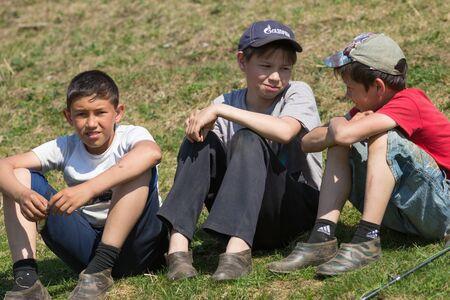River Ay, Republic of Bashkortostan 09-05-2019: three boys sit on the grass and talking Editorial