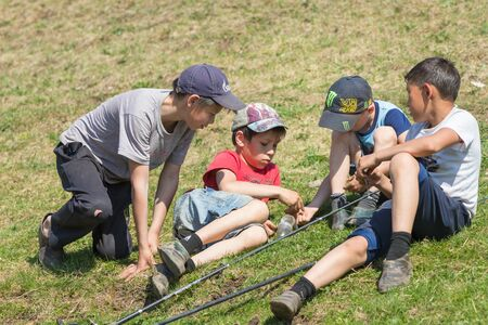 River Ay, Republic of Bashkortostan 09-05-2019: Four boys sit on the grass and prepare for fishing