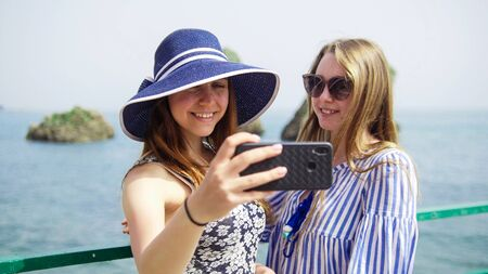 Two young smiling women take a selfie on the background of the sea on the phone - Mid shot