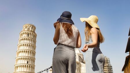 Two young women in panamas standing near the Leaning Tower and looking at it 免版税图像