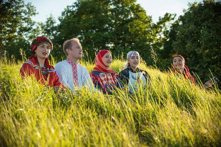 Gente sonriente en ropa tradicional rusa sentada en el campo de hierba alta