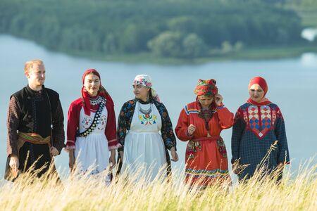 Leute in traditioneller russischer Kleidung, die auf dem Feld stehen - ein Mann, der eine Balalaika hält