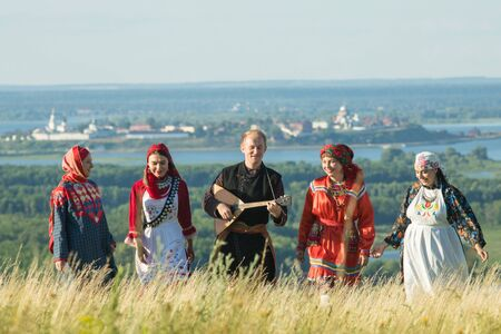 Smiling people in traditional russian clothes walking on the field - a man holding a balalaika