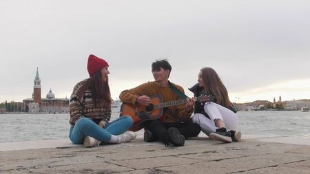 A group of young friends sitting on the edge of the quay and singing songs by the guitar - Venice, Italy