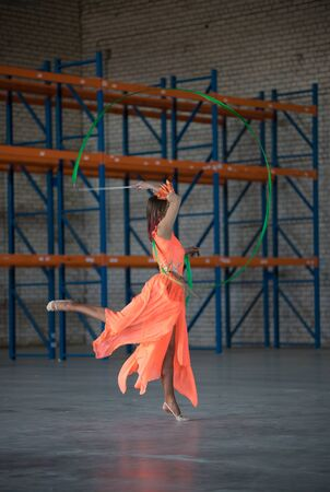 Young woman circus permomer dancing with gymnastic ribbon in hands in the warehouse