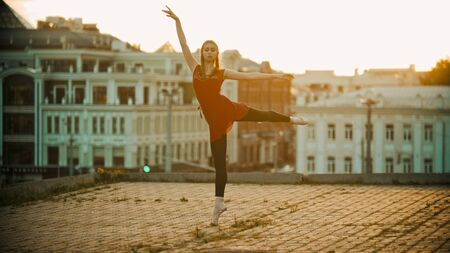 Young woman in red dress ballerina standing in the graceful pose on the roof - modern buildings on the background - bright sunset