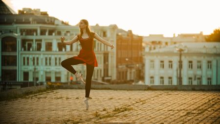 Young inspired woman in red dress ballerina standing in the graceful pose on the roof - modern buildings on the background - bright sunset Stock Photo