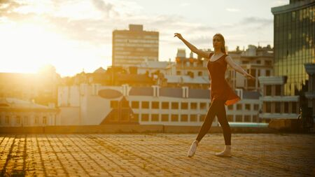 Young graceful woman in red dress ballerina standing in the pose on the roof - bright sunset