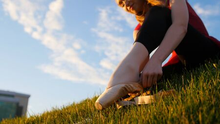 Young woman put on her pointe shoes - sitting on the green grass at sunset