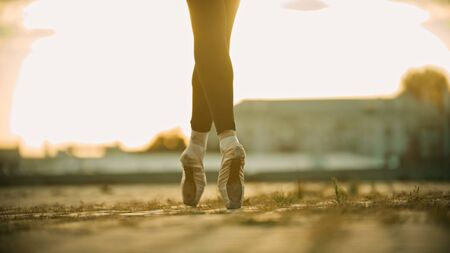 Graceful legs of young woman ballerina standing on the roof on her tiptoes - sunset