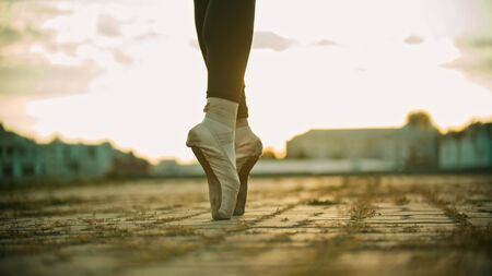 Feet of young woman ballerina standing on the roof on her tiptoes - sunset