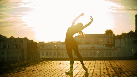 A silhouette of young woman ballerina in dress standing in the graceful pose on the roof on a background of modern buildings - bright sunset Stock Photo