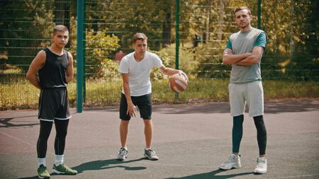 Three sportsmens standing on the basketball court outdoors and looking in the camera