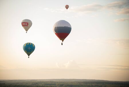 18-07-2019 Pereslavl-Zalessky, Russia: a different air balloons flying using heat. Different printed logos on balloons. Flying on a background of evening sky Banque d'images - 128214313