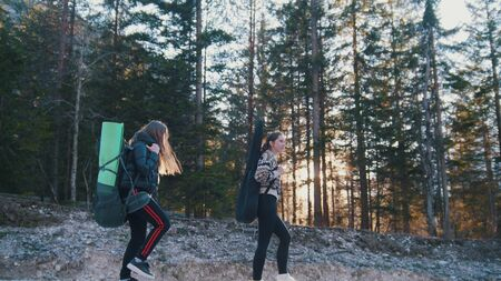 Two young women walking on the rocky road with the backpacks and guitar in the forest Imagens