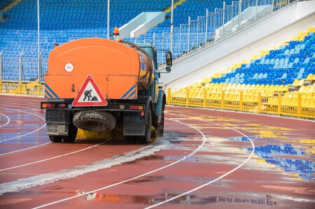 A big cleaning machine washes the running track with water stream in the stadium