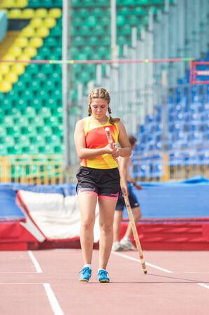 Pole vault - a female jumper preparing for the jump in the stadium Stockfoto