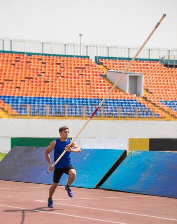 Pole vault - a young man runs up holding a pole