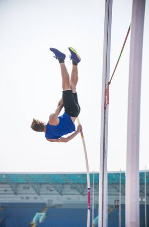 Pole vault - a young athletic man rest against the ground on the pole and ready to jump