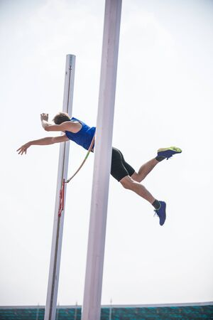 Pole vault - a young athletic man jumping over the bar 写真素材